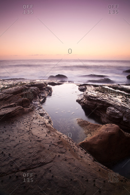 Tide pool in rocks at sunset