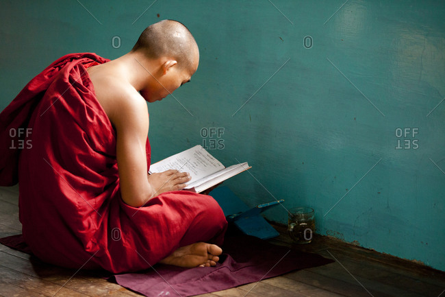 Kan Gyi, Myanmar - August 22, 2011: Monk studying by wall in Myanmar monastery