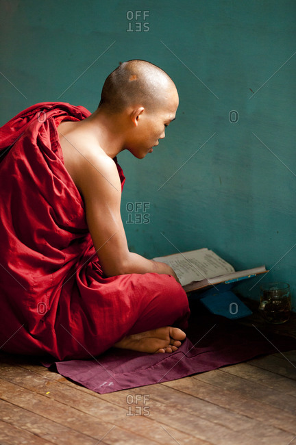 Kan Gyi, Myanmar - August 22, 2011: Monk studying on floor in Myanmar monastery