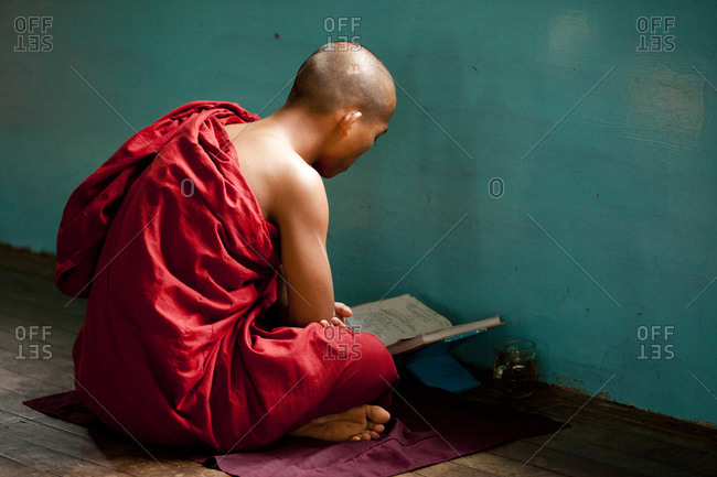 Kan Gyi, Myanmar - August 22, 2011: Young monk studying by wall in Myanmar monastery
