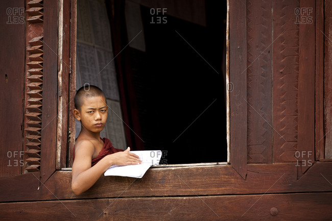 Kan Gyi, Myanmar - August 22, 2011: Novice monk reading at window at monastery