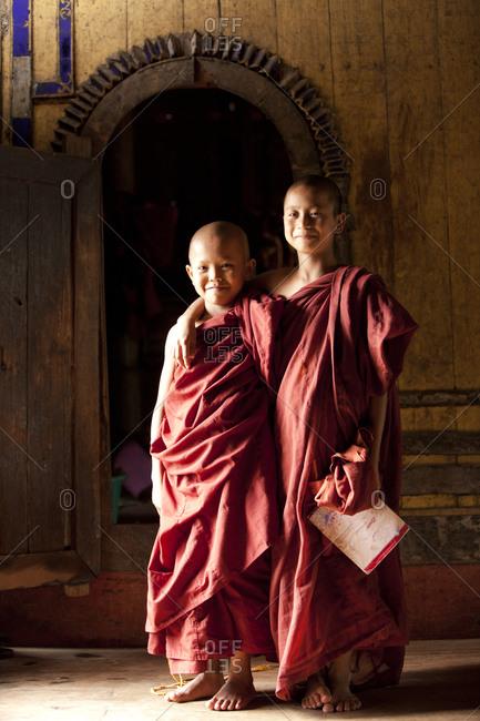 Kan Gyi, Myanmar - August 22, 2011: Two novice monks smiling in monastery in Myanmar
