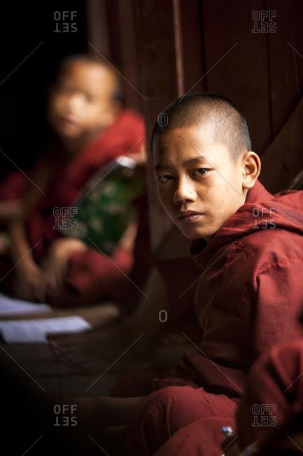 Kan Gyi, Myanmar - August 22, 2011: Novice monks sitting in monastery in Myanmar