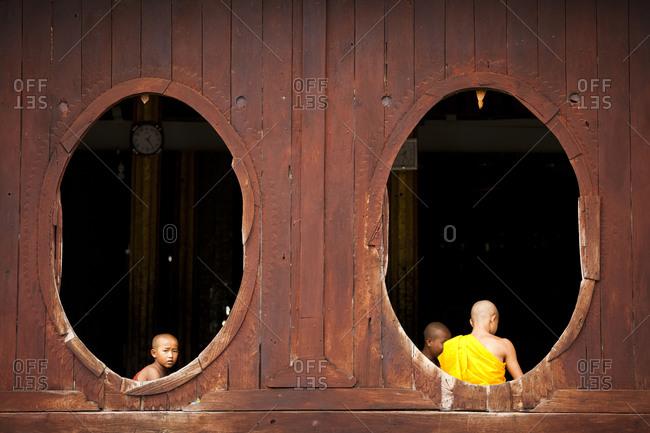 Bagan, Myanmar - August 24, 2011: Young buddhist monks by window of monastery in Myanmar