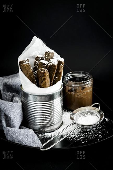 Bastoncini di castagne (chestnut biscotti) in a tin with powdered sugar and hazelnut creme
