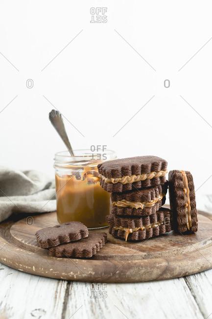 Side view of biscotti al dulche de leche with jar of caramel