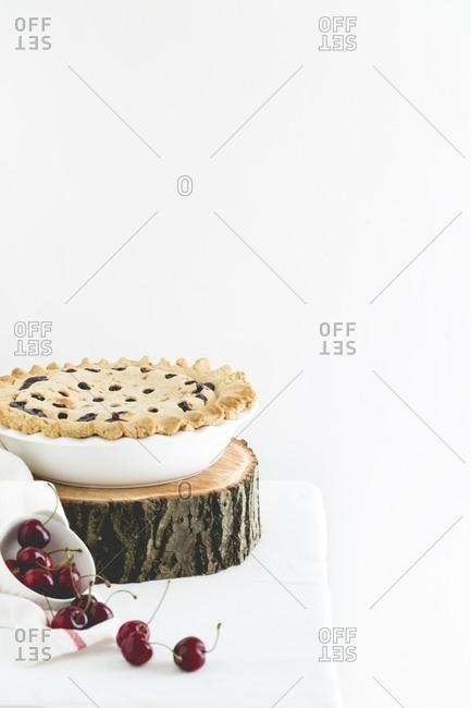 Cherry pie on slab of wood with cherries