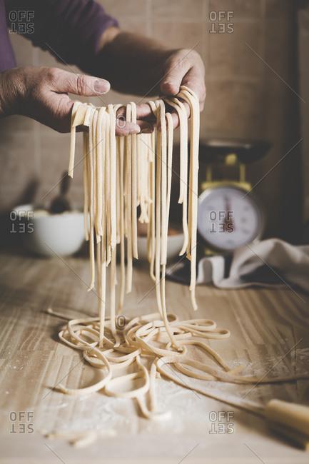 Hands holding freshly cut handmade pasta