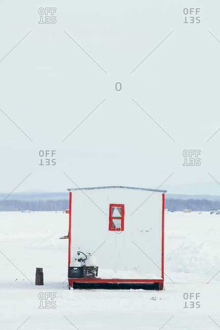 White and red ice fishing hut on frozen lake
