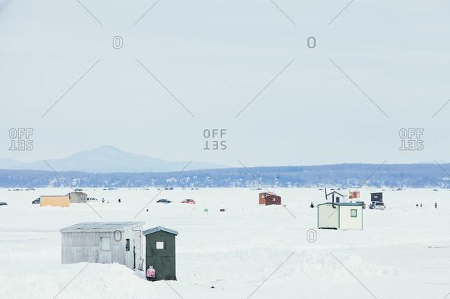 Ice fishing huts on a frozen lake