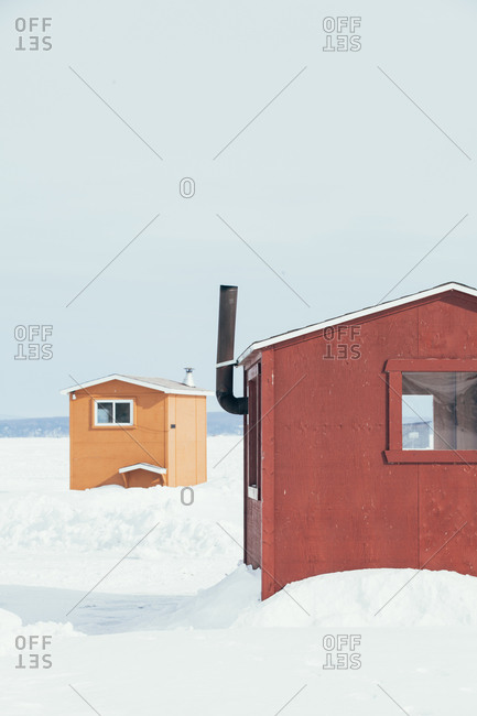 Rustic ice fishing shelters on a frozen lake