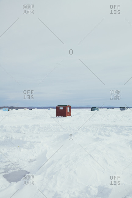 Distant view of cluster of fishing shanties and vehicles on the ice