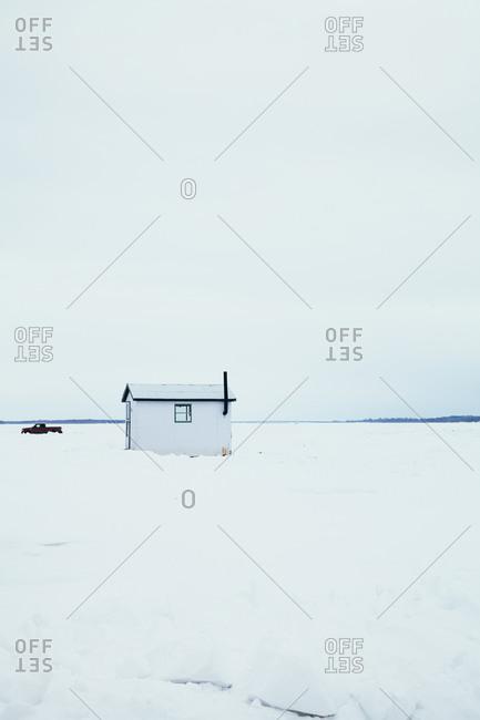 Fishing hut and pick up truck on a frozen lake