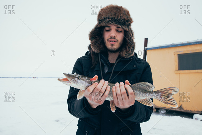 Ice fisherman holding a freshly caught pike