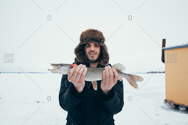 Proud ice fisherman holding his catch