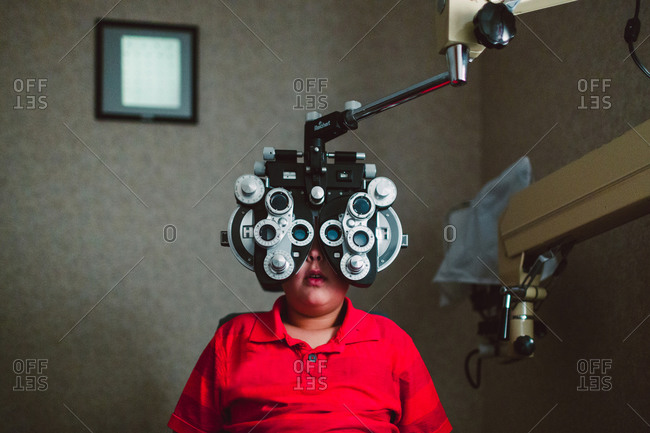 Boy at eye clinic with refraction machine