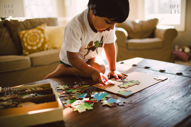 Young boy putting puzzle together at coffee table