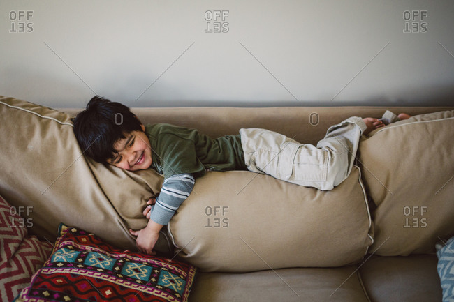 Boy sprawled out on couch cushions