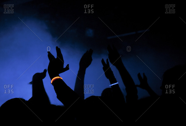 People at a concert raise up their arms