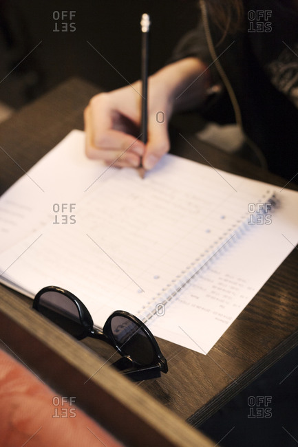 A woman writes in a notebook on a wood desk
