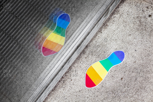 A rainbow footprint stuck on a sidewalk