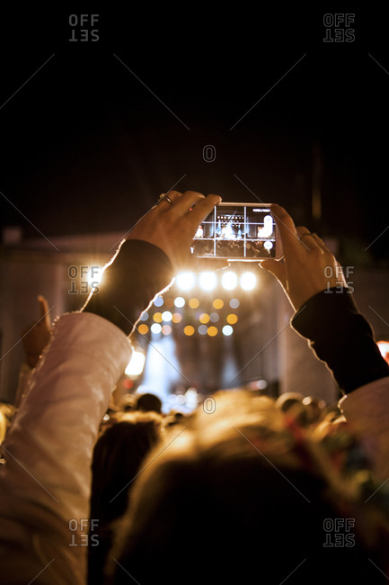 An audience member takes a photograph at a concert
