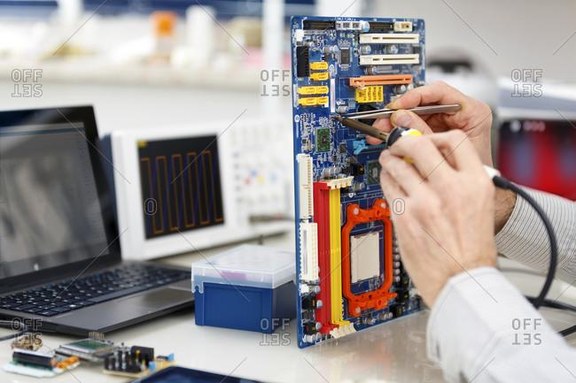 Person repairing a circuit board