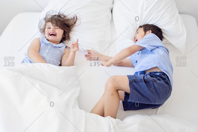 A boy and a girl giggle in bed
