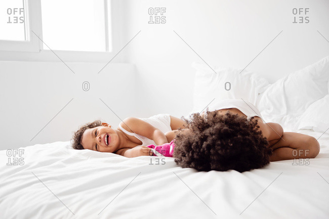 Two little girls collapse in laughter on a bed
