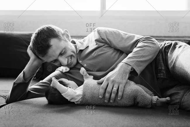 A dad lays with his newborn baby