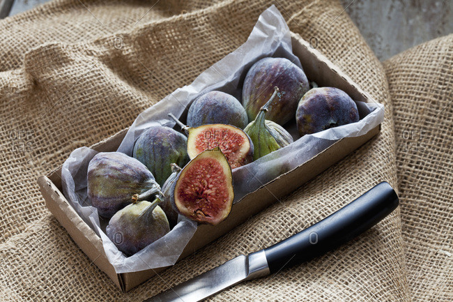 Cardboard box of figs and knife on jute