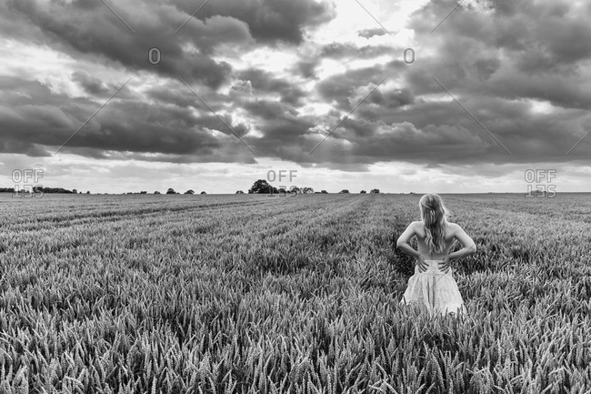 Young woman standing in grain field under dramatic sky