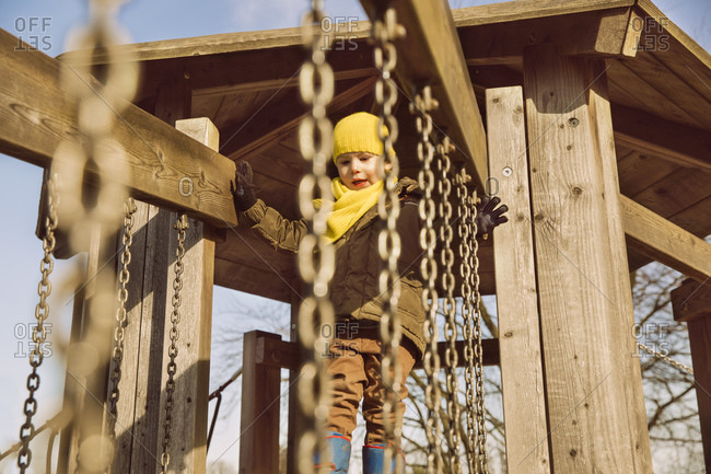 Little boy cautiously starting to walk along a hanging bridge on a playground