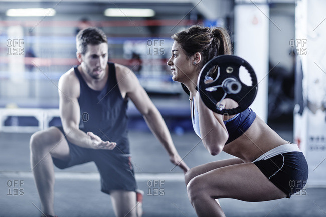 Trainer watching woman doing fitness training with weights