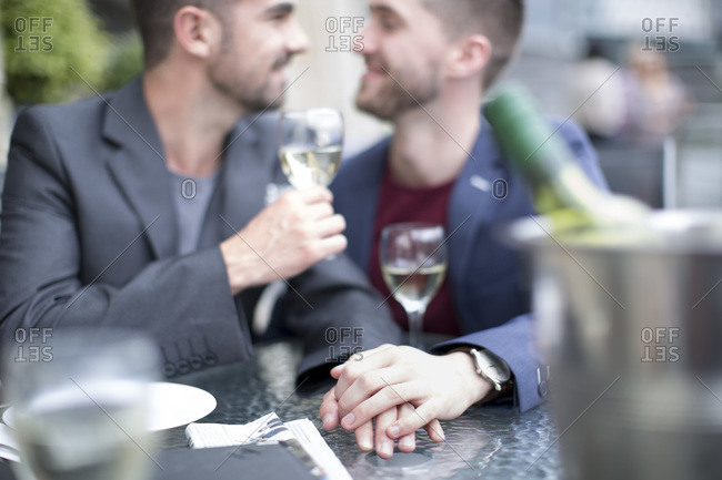 Gay couple sharing an intimate moment at a restaurant