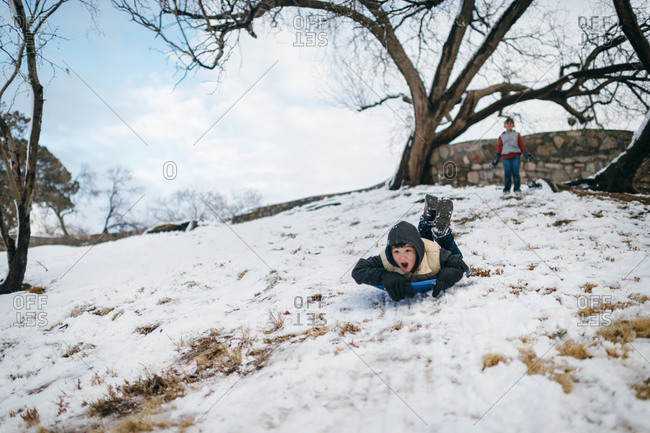 Child watches as boy sleds down a snowy hill