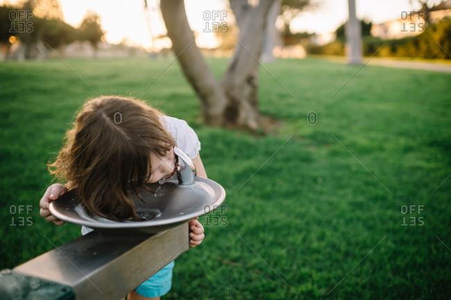 Girl getting drink from a park water fountain