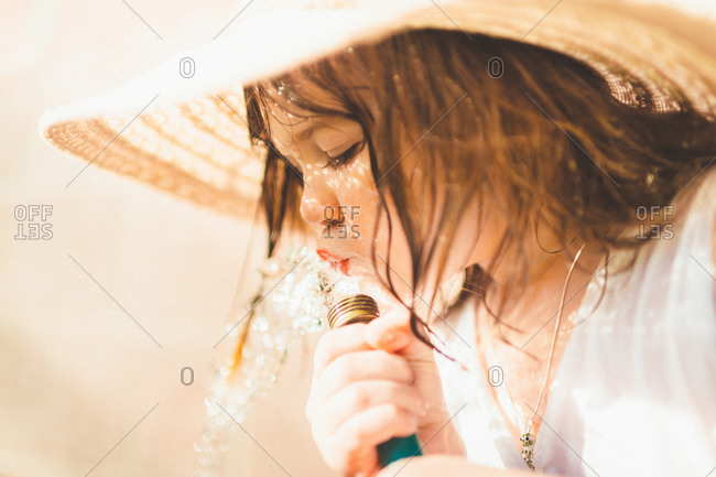 Girl in straw hat drinking from hose