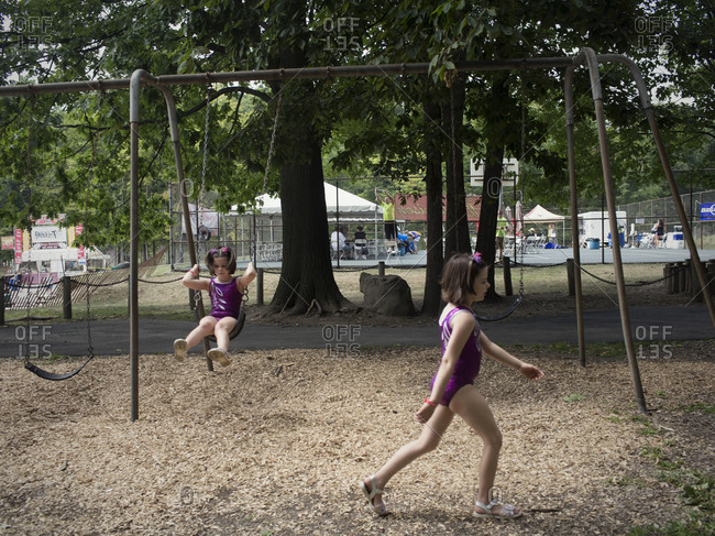 Twinsburg, Ohio - August, 2012: Two identical twins play in a park