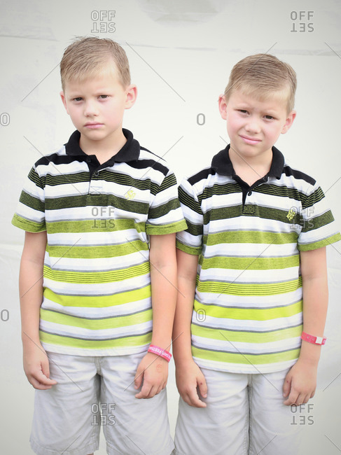 Twinsburg, Ohio - August 4, 2012: Two twin brothers grudgingly pose for a portrait