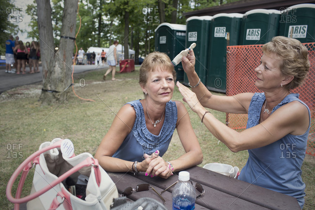 Twinsburg, Ohio - August 5, 2012: A woman combs her twin sister's hair during the annual Twins Days Festival