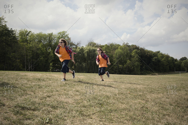 Twinsburg, Ohio - August 5, 2012: Twin brothers in plaid shirts run through a field at the annual Twins Days Festival
