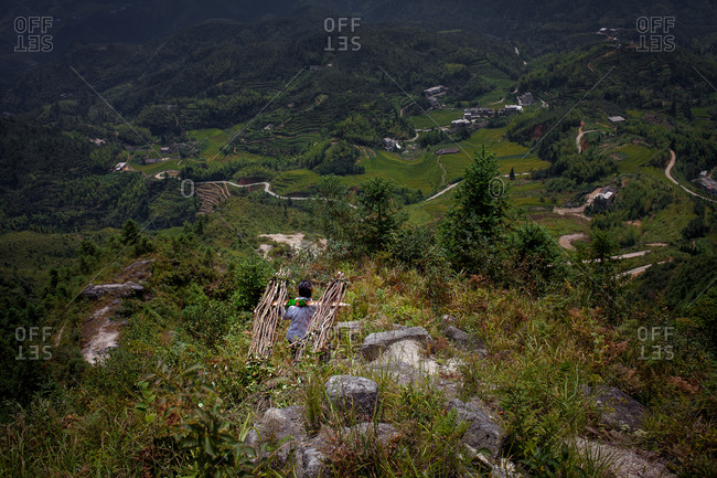 Chinese woman carrying stuck bundle down mountain