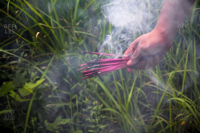 Hand holding burning incense stick over ground
