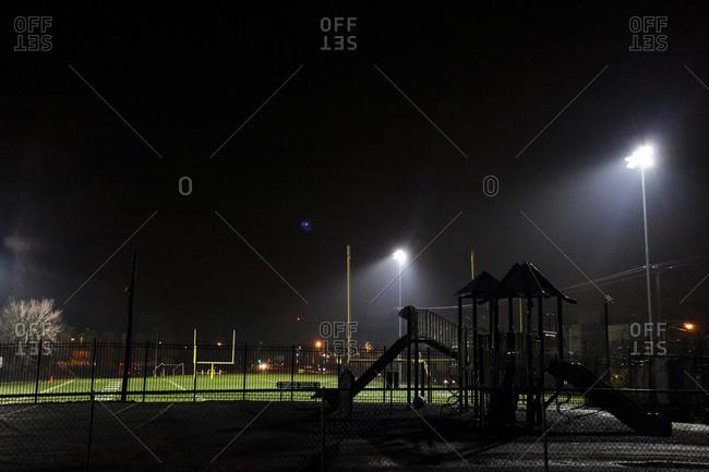 Empty school football field and playground at night