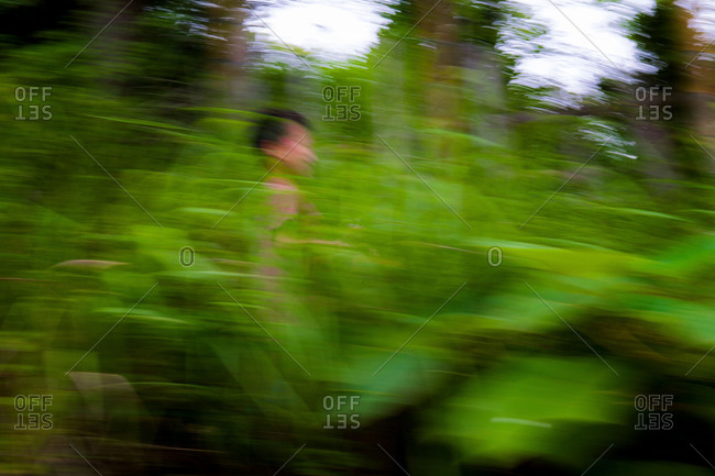 Young Chinese boy running through vegetation