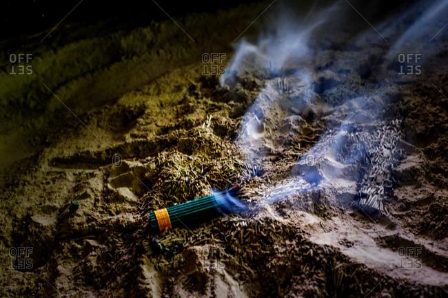 Bundle of incense burning at night on dirt