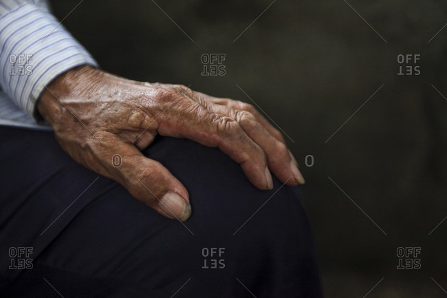 Hand of elderly Chinese man resting on his knee