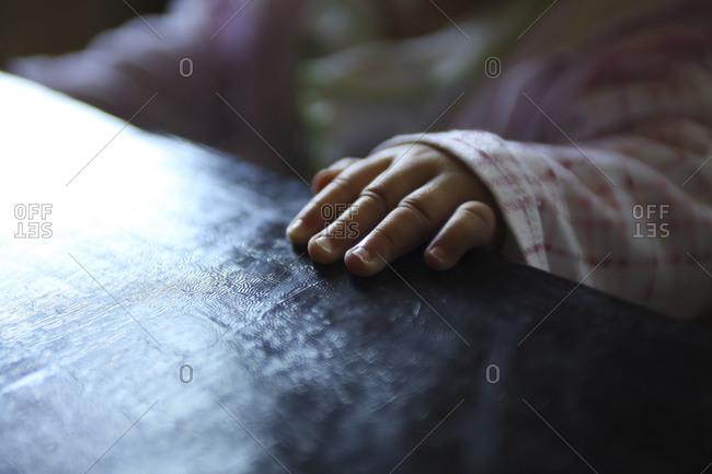 Little girl's hand resting on table
