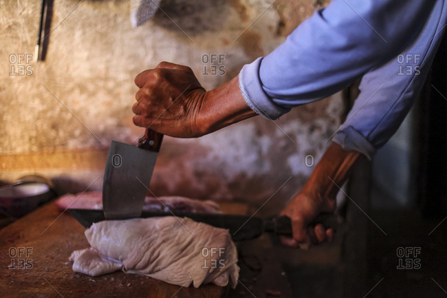 Man cutting meat in kitchen in China
